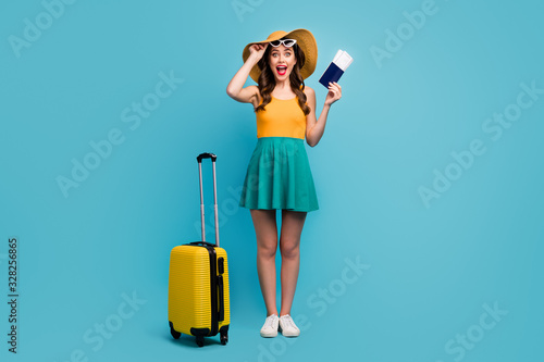 obraz PCV Full body photo of pretty lady traveler hold passport tickets rolling suitcase luggage airport cheap flights wear sun specs short summer dress headwear shoes isolated blue background