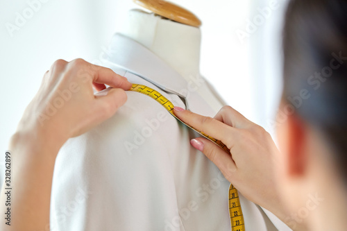 tailoring, sewing and clothing concept - close up of fashion designer measures jacket with tape measure