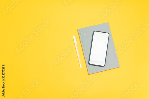 Top view of smartphone template with empty screen and grey notebook on yellow ba Canvas Print