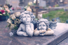 Two Angels In A Cemetery Above A Grave, Closeup Of Stone Angels