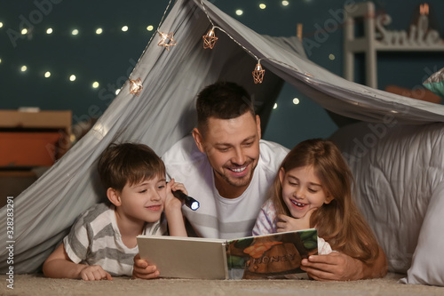Father and his little children reading bedtime story at home Wallpaper Mural