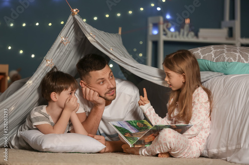 Father and his little children reading bedtime story at home Fototapet