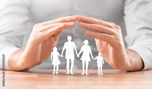 Leinwand Poster Family care concept. Hands with paper silhouette on table.