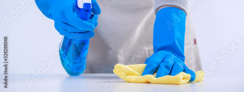 Fotografía Young woman housekeeper is doing cleaning white table in apron with blue gloves, spray cleaner, wet yellow rag, close up, copy space, blank design concept