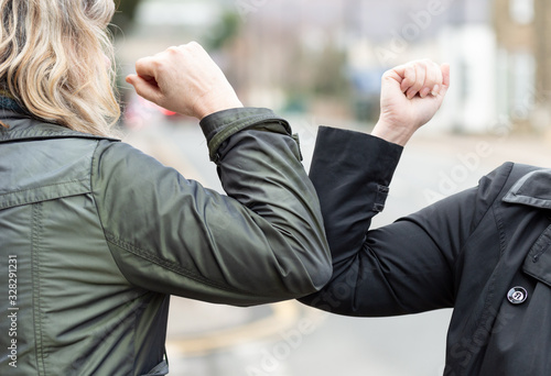 obraz dibond Elbow bump. New novel greeting to avoid the spread of coronavirus. Two women friends meet in a British street with bare hands. Instead of greeting with a hug or handshake, they bump elbows instead.