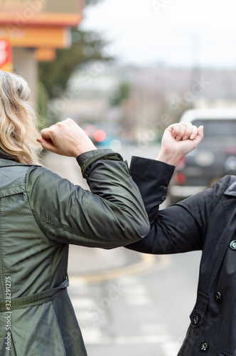 obraz dibond Elbow bump. New greeting to avoid the spread of coronavirus. Two women friends meet in British street with bare hands. Instead of greeting with a hug or handshake, they bump elbows instead. Vertical.