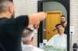 Young barber cutting old man's hair, having a good time. Closep up