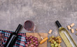 Top view wine bottles with glass on sackcloth and copy space on dark stone background horizontal