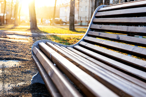 Wooden brown bench with a back in the Park against the background of a bright sunset Wallpaper Mural