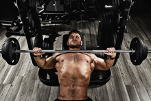 Young Muscular Man Lifting A Barbell Bench Press In The Gym. Beautiful Body, Goal Achievement, Sport As A Way Of Life.