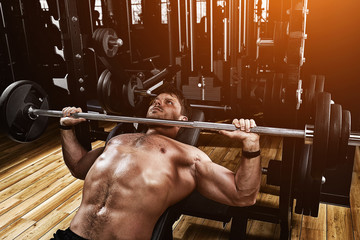 Fototapeta na wymiar Young muscular man lifting a barbell bench press in the gym. Beautiful body, goal achievement, Sport as a way of life.