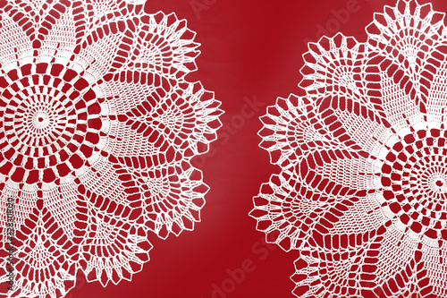 Photo Two handmade crocheted white lace napkins isolated on red background
