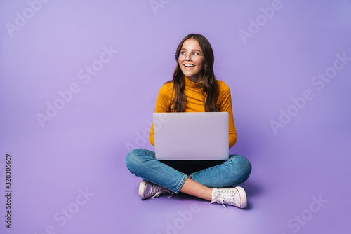 Image of young woman using laptop while sitting with legs crossed