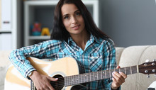 Beautiful Girl With Acoustic Guitar In Her Hands. Learning To Play Instrument, Basic Chords. Girl Devotes Time To Hobby That Relaxes Her. Singing Song With Live Instrumental Accompaniment