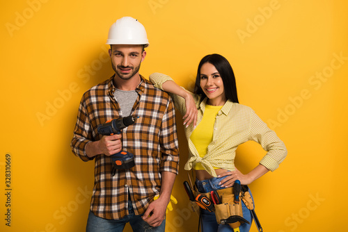 Obraz professional smiling manual workers with tool belt holding electric drill on yellow - fototapety do salonu