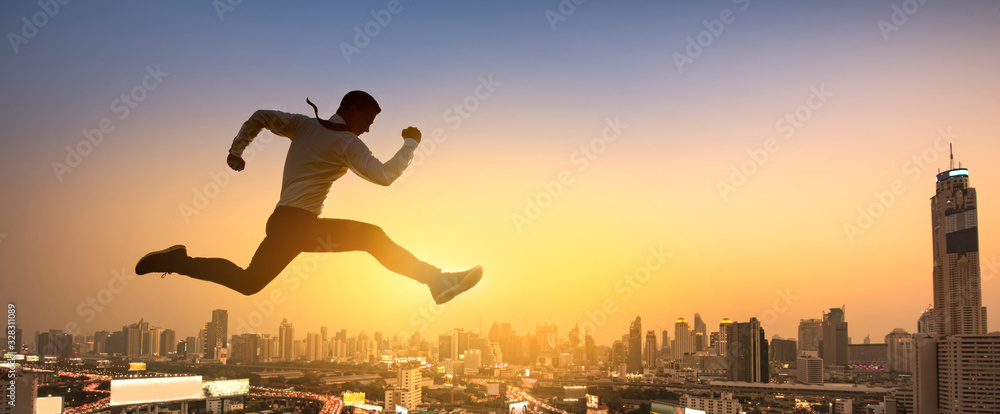 Fototapeta Young businessman jumping high, Work, job, or successful business concept. Cityscape background.
