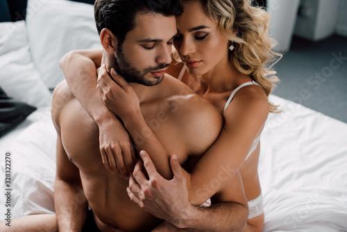 Fototapeta Seductive woman in lingerie hugging handsome boyfriend on bed obraz