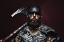 Portrait Of A Viking Man With An Axe. A Man Of 30 Years Holds A Large Battle Axe On His Shoulder. Warrior Dressed In An Authentic Suit