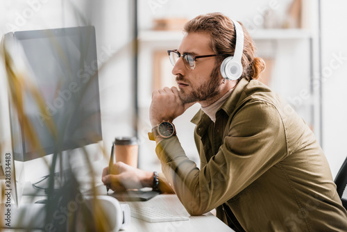 Side view of 3d artist in headphones using graphics tablet and looking at computer monitor on table