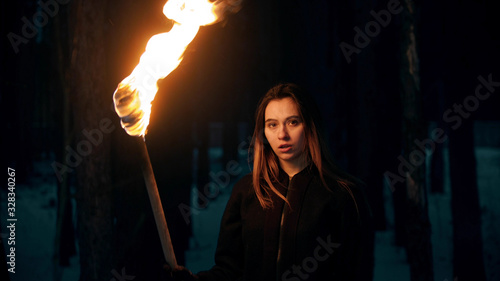 Valokuva Young woman with torch posing in night forest