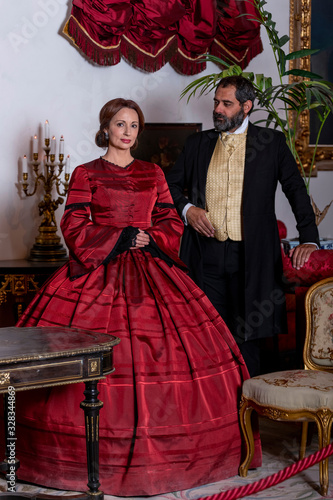 Photographie A woman and a man, elegantly dressed, in 19th-century-style clothes, pose standi