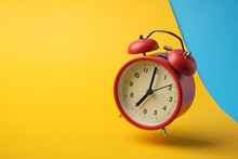 Red Retro Alarm Clock Floating In The Air With Yellow And Blue Background.