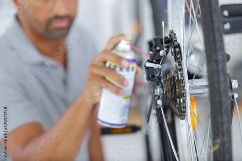 man hands spraying an oil to a bike chain Fototapete