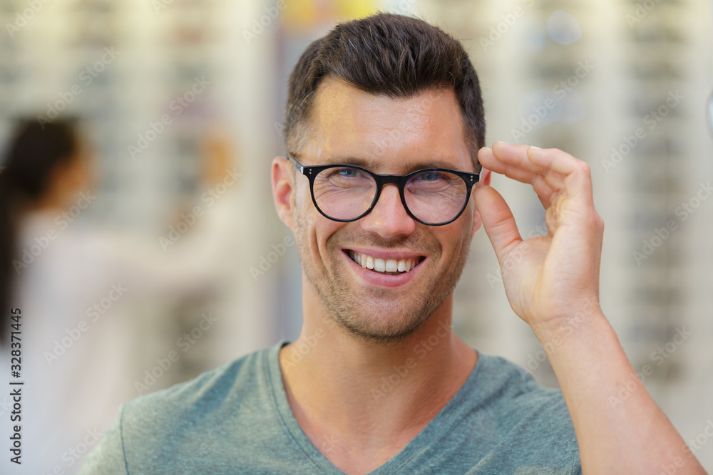 Fototapeta handsome man choosing glasses in optics store