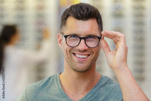 Fototapeta handsome man choosing glasses in optics store obraz