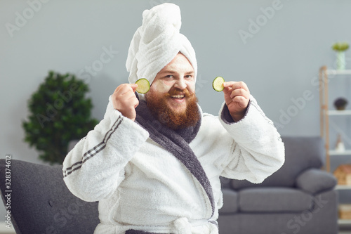 Funny strange fat bearded man with a cosmetic mask on his face in a bathrobe doe Fotobehang