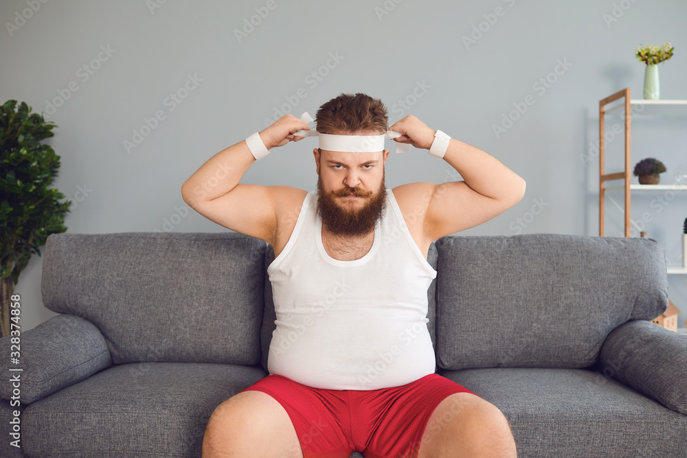 Fototapeta Funny fat man in sportswear is sitting on the sofa in the room