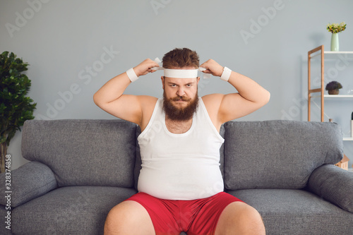 Funny fat man in sportswear is sitting on the sofa in the room Fototapete