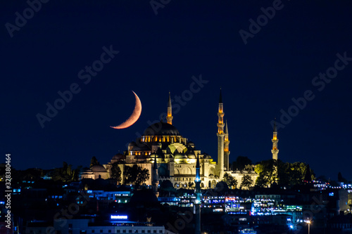 Photo The moon stands like a crescent moon over the Fatih Mosque at night