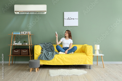 Photo Young woman switching on air conditioner at home