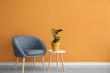 Leinwanddruck Bild - Comfortable armchair and table with houseplant near color wall