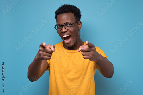 Handsome young african man in yellow clothes pointing his finger at you фототапет