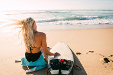 Woman Sitting Next To Surfboard On Beach