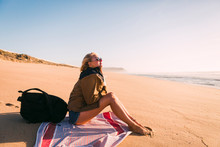 Woman Sitting On Towel On Beach
