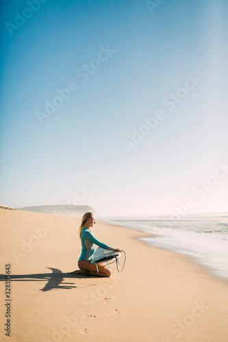 Woman kneeling holding surfboard on beach - 328395643