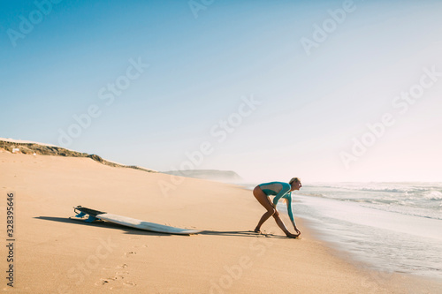 Woman wearing wetsuit stretching on beach - 328395646