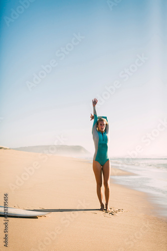 Woman wearing wetsuit stretching on beach - 328395656