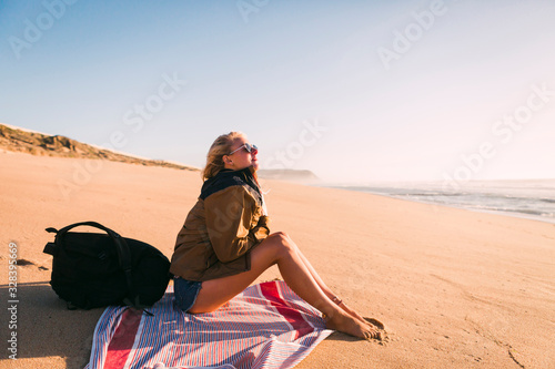 Woman sitting on towel on beach - 328395669