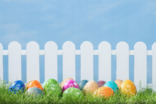 Spring Grass And Wooden Fence With Easter Eggs On Cloudy Sky