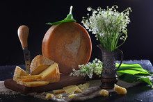 A Cheese Knife And Chunks Of Hard Cheese With A Bouquet Of Lilies Of The Valley On A Black Background. Copy Space.