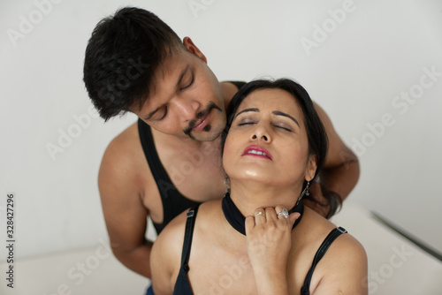 Obraz na plátně Attractive Indian Bengali brunette couple seductive foreplay in black dress in white bedroom while the man trying to strangle the throat of the girl from her back