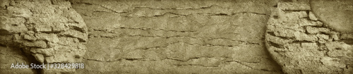 Light brown stone background. Old cracked wall. Grunge banner. Sepia. Vintage wall background with copy space. Website header.