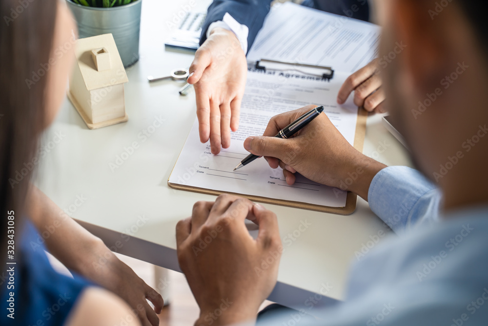 Fototapeta Young Asian couple making contract with house sale agency. Man signing the contract and his wife sitting next to him looking the contract document with smile. Real estate agreement successful concept.