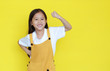 Happy asian little child girl showing his muscle with looking camera isolated on yellow background with copy space. Strong kid in dungarees with good health concept