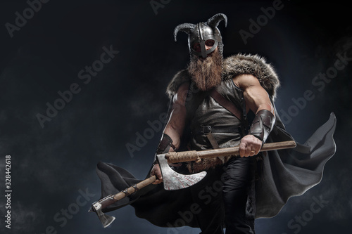 Photo Warrior Viking in full arms with axe and shield on dark background