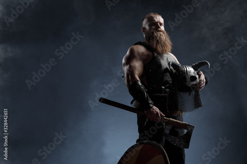 Medieval warrior berserk Viking with tattoo with axes attacks enemy Canvas Print